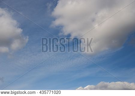 Light White Clouds Fly Across A Bright Blue Sky. Clear Sky At Sunny Summer Afternoon. Spring Cloudsc