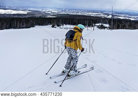 Young Woman In Yellow Jacket And Ski Helmet Skiing On A Mountain Slope, Winter Sports, Alpine Skiing