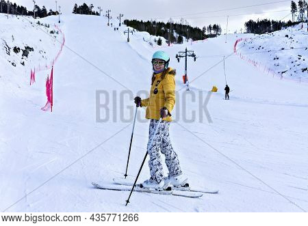 Happy Smiling Young Woman In Yellow Jacket And Ski Helmet Downhill Skiing On A Mountain Slope, Winte