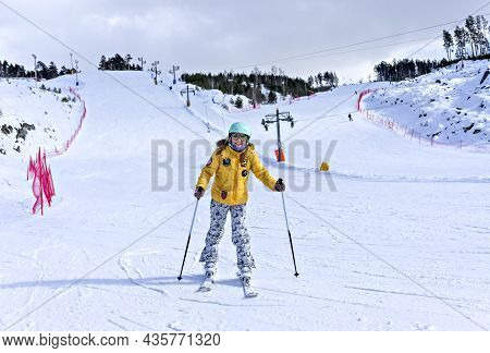 Happy Smiling Young Woman In Yellow Jacket And Ski Helmet Skiing On A Mountain Slope, Winter Sports,