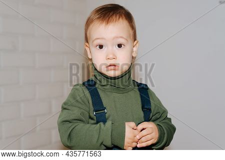 Portrait Of Little Cute Boy In Green Sweater Standing Indoors Against White Wall And Looking At Came