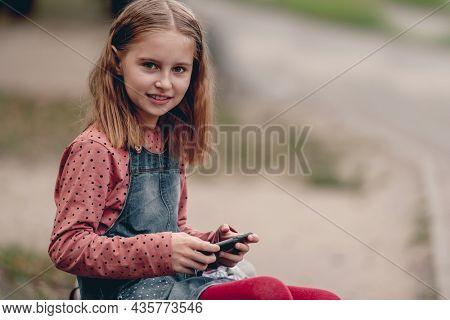 Pretty girl kid autumn portrait outdoors. Preteen female child closes coat at the street