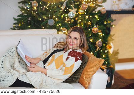 Happy Caucasian Joyful 50s Woman Sitting Covered With Warm Knitted Blanket On White Cozy Sofa On Cus