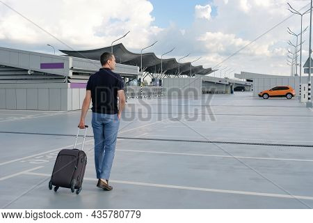 A Young Man With A Suitcase Goes To The Airport Parking Lot. Travel Concept