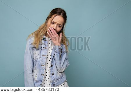 Photo Of Young Tired Weary Beautiful Blonde Woman With Sincere Emotions Wearing Denim Blue Jacket Is