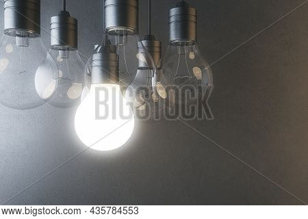 Glowing Light Bulb On Blurry Concrete Wall Background. Idea, Innovation, Solution And Invention Conc