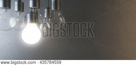 Glowing Light Bulb On Blurry Wide Concrete Wall Background. Idea, Innovation, Solution And Invention