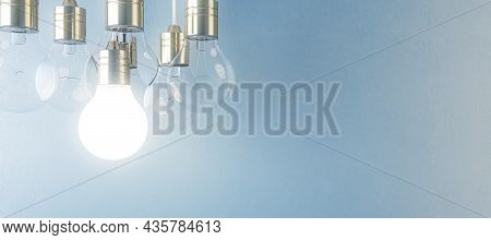 Glowing Light Bulb On Blurry Wide Blue Wall Background. Idea, Innovation, Solution And Invention Con