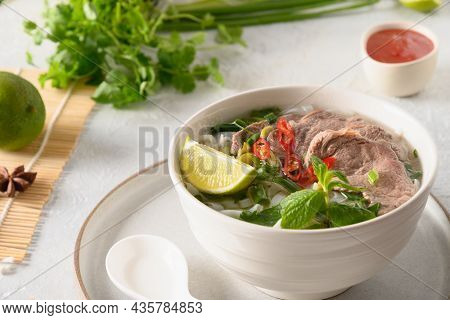 Pho Bo Soup With Beef In White Bowl On Light Background. Vietnamese Cuisine.