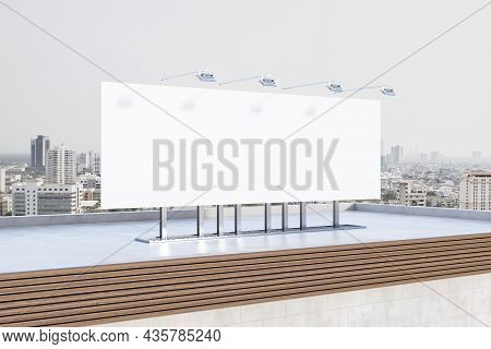 Empty White Billboard Banner On Rooftop With City In Daylight In The Background. Outdoor Advertiseme