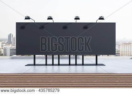 Empty Black Billboard Poster With Lamps On Rooftop With City In Daylight In The Background. Outdoor