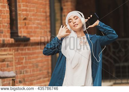 Middle Eastern Woman In Hijab Listening Music With Headphones And Dancing Outdoors. Woman Independen
