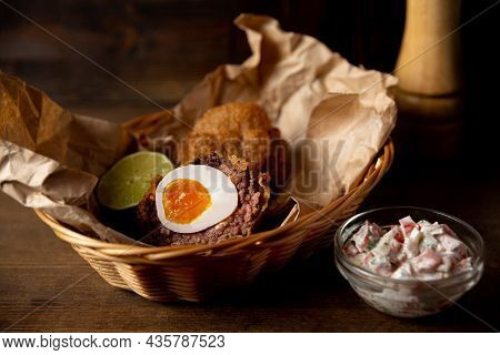 Portion Of Scotch Egg And Pico De Gallo Sauce Served On сraft Paper And Wicker Basket. Fried Pub Foo