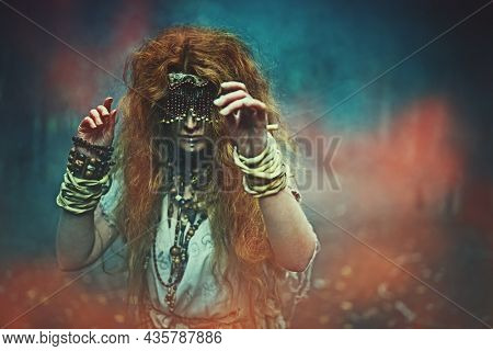 A frightening forest witch with a mask on her eyes doing a mysterious ritual in a dark gloomy forest. Woman shaman. Paganism. Death ritual. Halloween.