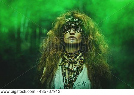 Portrait of a frightening forest witch with a mask covering her eyes in a gloomy forest surrounded by mystical green haze. Woman shaman. Paganism. Death ritual. Halloween.
