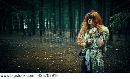 Mysterious forest witch with a mask covering her eyes standing in a dark gloomy forest. Woman shaman. Paganism. Death ritual. Halloween. Copy space.