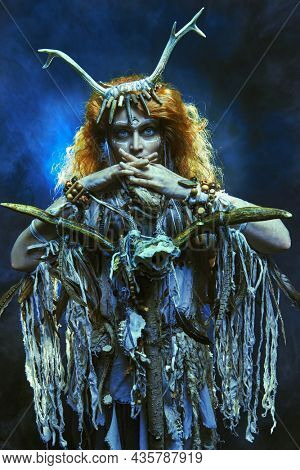 Portrait of a shaman woman with bright blue eyes in ritual clothes posing with a shaman staff in the dark background surrounded by a mystical haze. Ethnic traditions. Paganism. Halloween.