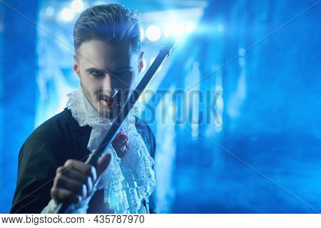Evil bloodthirsty vampire poses in his old castle with mysterious haze all around holding a magic wand in his hand being up to something bad. Halloween. Vampires. Copy space.