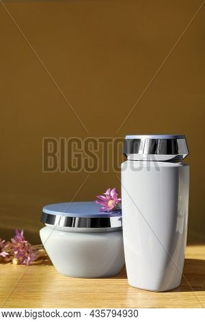 Hair Care Cosmetic Products And Beautiful Flowers On Wooden Table