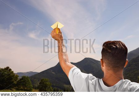 Man Throwing Paper Plane In Mountains On Sunny Day. Space For Text