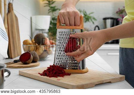 Woman Grating Fresh Beetroot At Kitchen Counter, Closeup