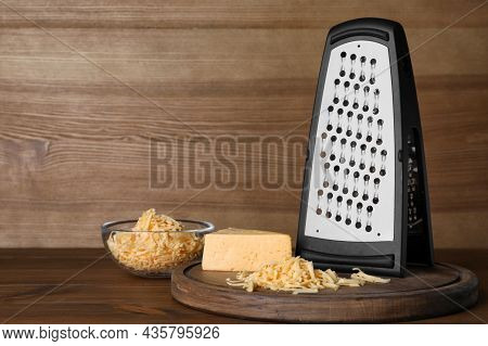Grater And Delicious Cheese On Wooden Table. Space For Text