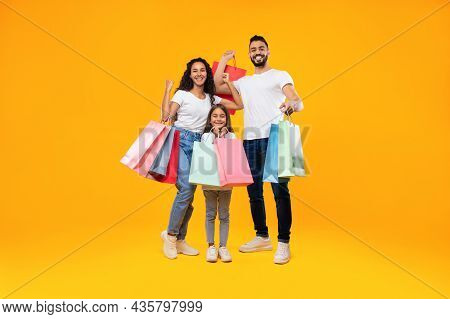 Arab Family Shopping Together Holding Colorful Shopper Bags, Yellow Background