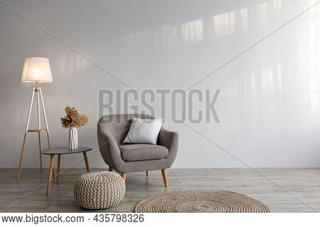 Cozy Armchair With Pillow, Luminous Lamp, Table, Dry Plants In Vase, Ottoman And Carpet On Floor On