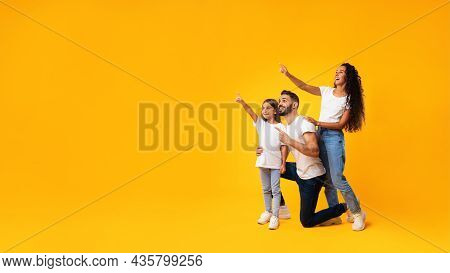 Excited Middle-eastern Family Pointing Finger Aside Over Yellow Background, Panorama