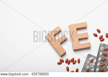 Wooden Letters Fe And Pills On White Background, Top View. Anemia Concept