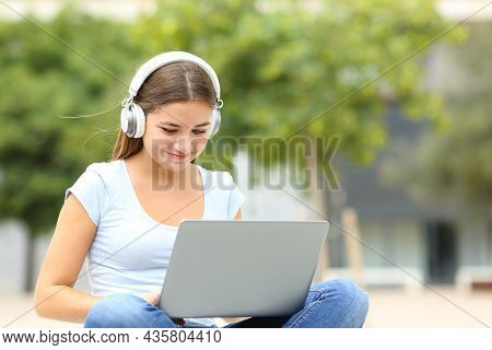Happy Student Elearning Using Laptop And Headphones Sitting In A Campus