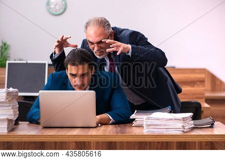 Old male employer and young male assistant in bullying concept