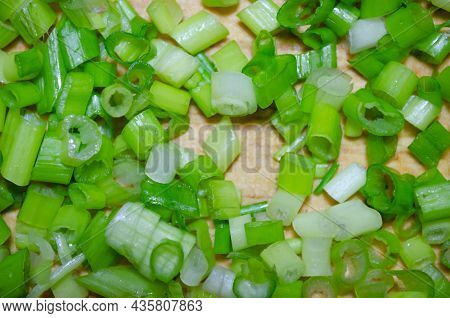 Finely Cut Green Onions On A Wooden Board For Cutting Vegetables In Close-up Macro