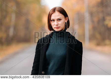 Portrait Of A Girl In The Autumn Forest. A Young Woman With Short Hair In A Black Coat Is Walking In