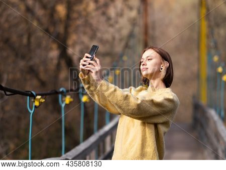 A Girl Blogger Is Broadcasting Live On A Mobile Phone In An Autumn Forest. Young Woman Looks Into Th