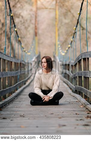 A Lonely Girl Sits On A Bridge In The Autumn Forest. Young Woman Walks In The Park In A Sweater.