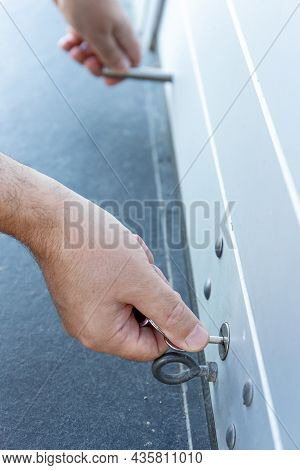 Close Up Of A Hand With A Key Closing A Roller Shutter Door Of A Store. Closing Concept
