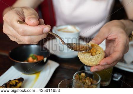 Close Up Of Customer Filling Chili Sauce Into Hollow Of Panipuri A Popular Indian Street Food. Panip