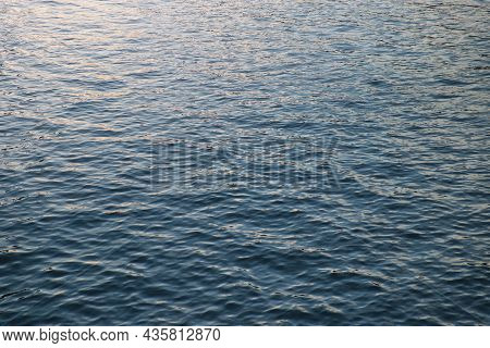 Calm Ripple On Water Surface. River, Lake, Pond, Sea Pure Blue Water. Warm Evening Light On The Wate