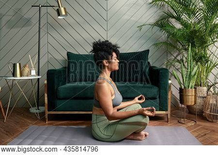 Healthy woman meditating in the living room