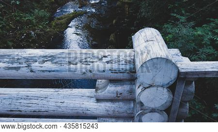 Detail Of Wooden Bridge Fencing Made Of Logs. River On Background