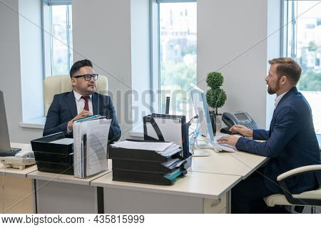 Two contemporary businessmen interacting while sitting by their workplaces