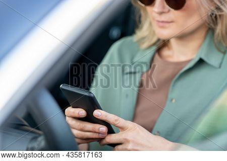 Hands of elegant female scrolling in smartphone while sitting by steering wheel in car