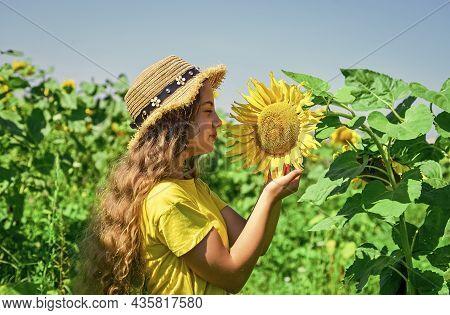 Happy Childhood. Beautiful Girl Wear Straw Summer Hat In Field. Pretty Kid With Flower. Beauty Of Su