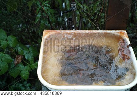 An Old Sink With Clogged Drain Hole And Leaking, Water, Outdoor Closeup