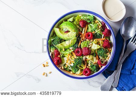 Summer Broccoli Salad With Raspberries, Pine Nuts And Avocado, Copy Space. Vegan Food Concept.