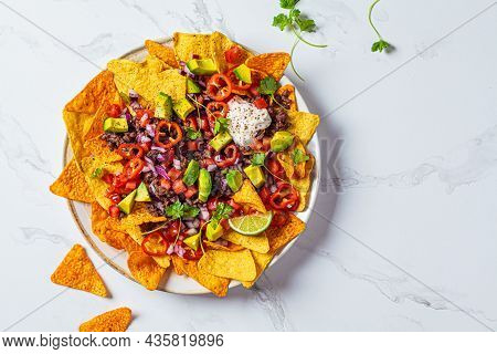 Mexican Food Concept. Corn Nachos Chips With Avocado, Pepper, Salsa And Grilled Minced Beef On White
