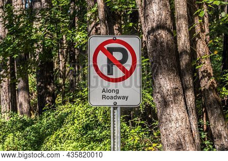 A No Parking Sign Symbol With Added Words Of Along Roadway Signage On A Post In The Park Along The F