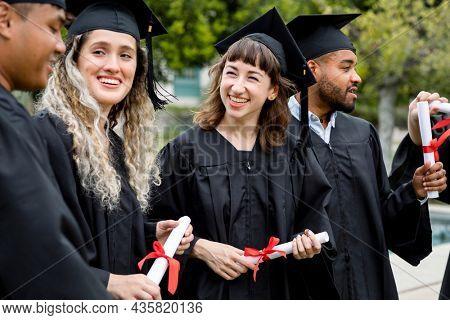 Happy students graduating university, celebrating with diplomas