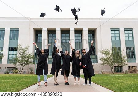 Graduating students throwing graduation caps in the air